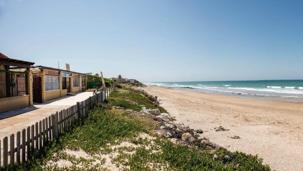 La playa La Ballena / Las Tres Piedras se encuentra en el municipio de Rota, perteneciente a la provincia de Cádiz y a la comunidad autónoma de Andalucía